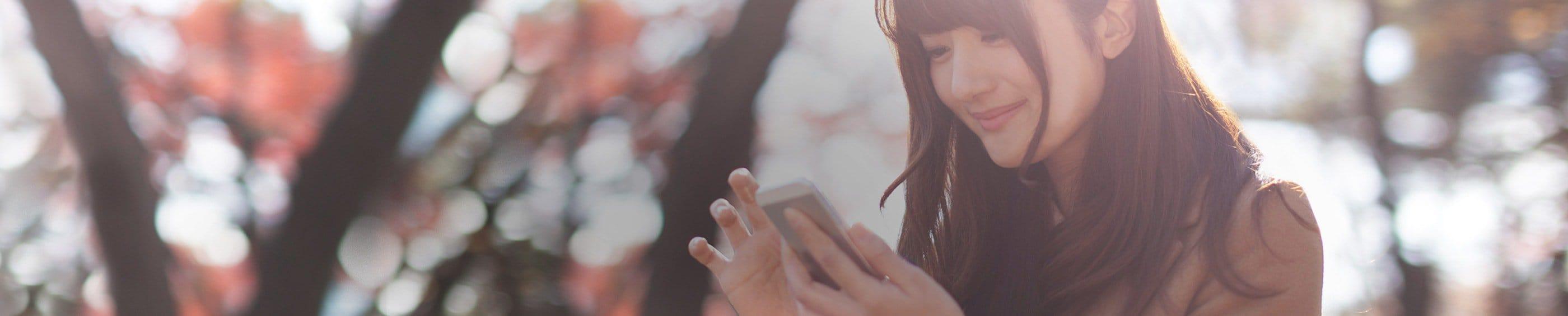 Una mujer joven en exteriores mirando su teléfono