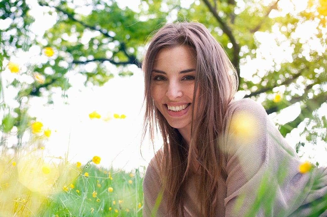 Una mujer adulta sonriendo mientras esta acostada en la grama con el sol brillando