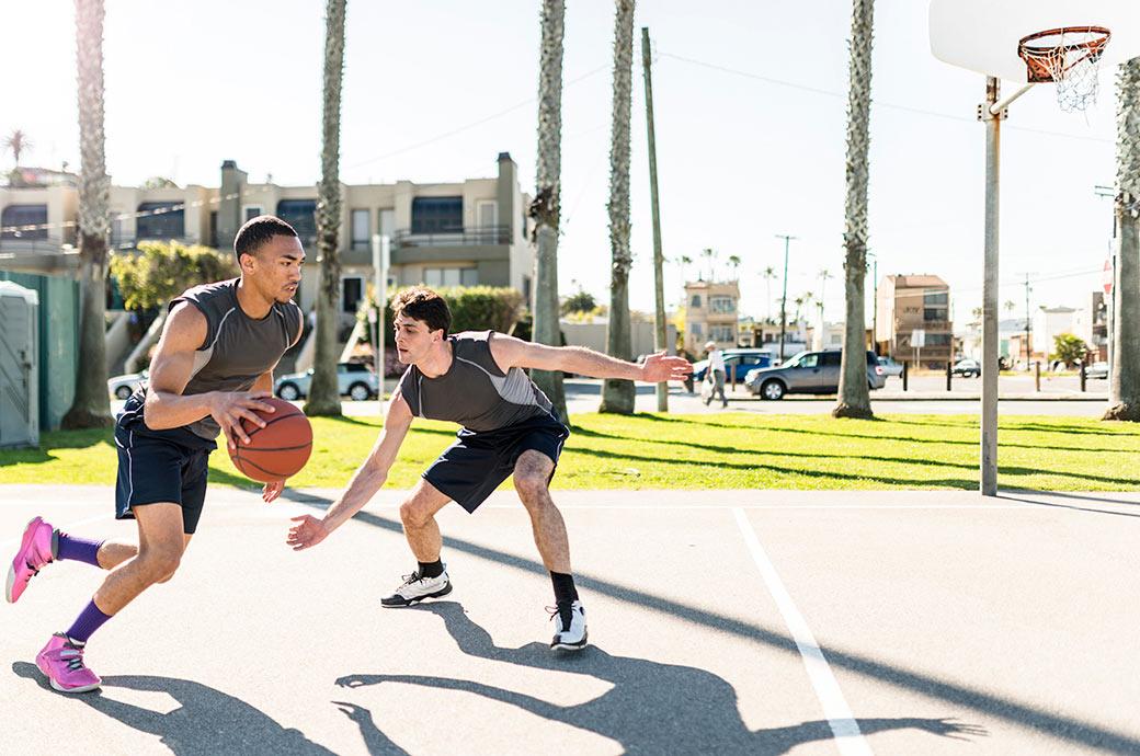 Dos chicos jugando basketball en el parque