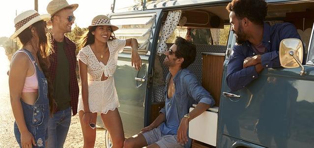Un grupo de amigos pasando el rato en su camioneta riendo y sonriendo