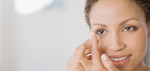 Una mujer con un lente de contacto en su dedo a punto de ponerlo en su ojo