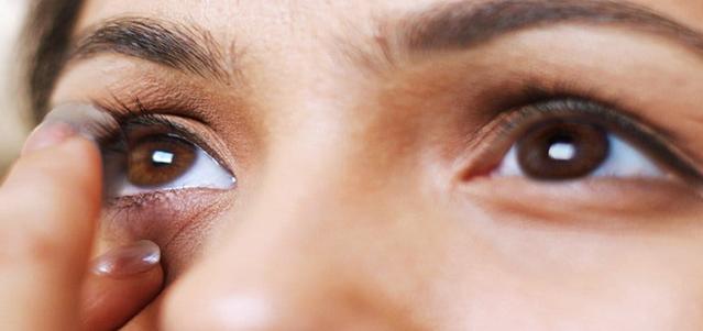 Un acercamiento de una mujer joven que se mira en un espejo poniéndose sus lentes de contacto
