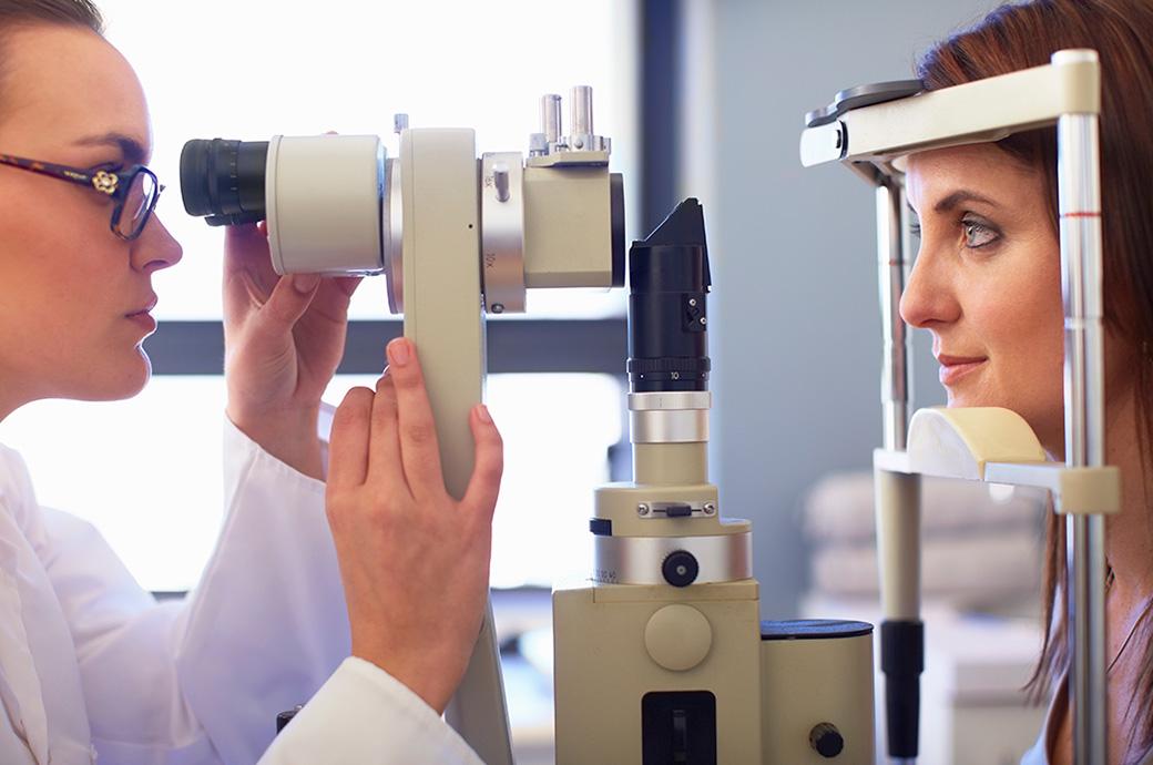 Una vista lateral de un oftalmólogo y una mujer joven mirando a través de una cámara de retina